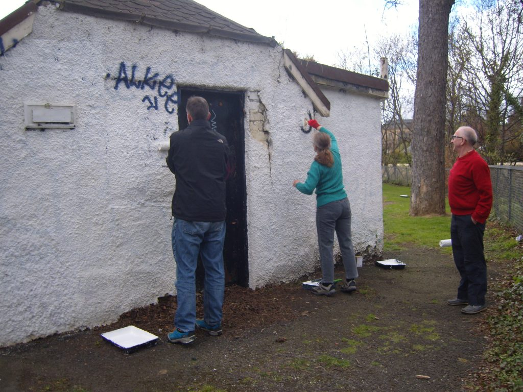 FoRP members painting over graffiti on pavilion